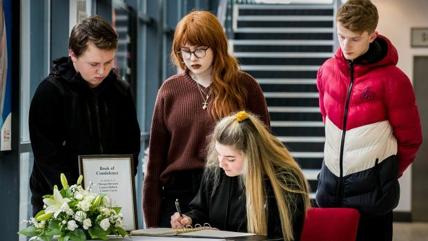 Alice Lambert with her fellow performing arts students at South West College Cookstown sign a Book of Condolence in Cookstown. Photograph: Liam McBurney/PA
