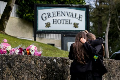 TIME TO REFLECT: Students from Holy Trinity College embrace and leave floral tributes outside the Greenvale Hotel in Cookstown, Co Tyrone, after the deaths of three teenagers, Lauren Bullock, Connor Currie and Morgan Barnard, at a St Patrick's night event at the hotel. Photograph: Liam McBurney/PA Wire
