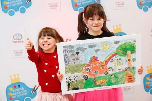 FLOWER POWER: Ciara Clarke (3) with her sister, finalist Lanah (5), from Galway, with her winning artwork 'Flower Power The Bee Saver Car' at the Toyota Dream Car Art Contest ceremony at Toyota Ireland's head office. Nine children were announced as the Irish finalists and will compete against international winners in Japan in August. Photograph: Conor McCabe Photography