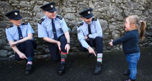 ROCK YOUR SOCKS: Garda Jean Tierney, Garda Fergus Collins and Sgt David Scahill from the Tullamore Community Policing Unit, who are taking part in the Rock Your Socks Campaign for Offaly Down Syndrome, meet Chloe Crombie (3) to mark World Down Syndrome Day on March 21st. Photograph: James Crombie/Inpho