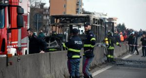 Firefighters and police officers stand by the gutted remains of a bus in San Donato Milanese, near Milan, Italy.  Photograpgh: Daniele Bennati/ANSA via AP