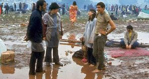 Young people standing in the mud and water and talking, during Woodstock in August, 1969. Photograph: John Dominis/The LIFE Picture Collection/Getty
