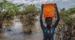 A girl fetches water from a river created by flood water   in the Nsanje district of southern Malawi. Photograph: Amos Gumulira/AFP/Getty Images