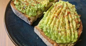 Homemade avocado smash toast topped with lemon and chili flakes.