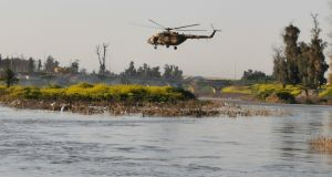An Iraqi rescue helicopter searches for survivors at the site where an overloaded ferry sank in the Tigris river near Mosul in Iraq. Photograph: Reuters