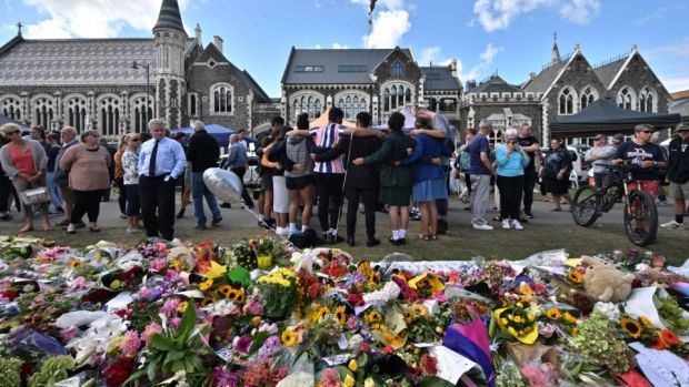 A group of students (centre) sings in front of flowers left in tribute to victims at the Botanical Garden in Christchurch on March 19, 2019, four days after a shooting incident at two mosques in the city claimed the lives of 50 people. Photograph: Anthony Wallace/AFP/Getty