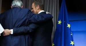 European Commission president Jean-Claude Juncker and European Council president Donald Tusk embrace after a joint news conference in Brussels. Photograph: Yves Herman/Reuters