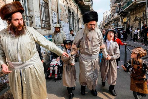 Ultra-Orthodox Jewish men and children wearing Purim costumes dance in the Jerusalem Mea Shaarim neighbourhood. The carnival-like holiday is celebrated with parades and costume parties to commemorate the deliverance of the Jewish people from a plot to exterminate them in the ancient Persian Empire, 2,500 years ago, as recorded in the Biblical Book of Esther. Photograph: Menahem Kahana/AFP/Getty Images