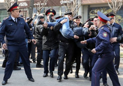 Police officers detain an anti-government protester during a rally in Almaty, Kazakhstan. Media reports say that protestors have been detained after taking a stance against a proposed name change for the country's capital from Astana to Nursultan, after the outgoing president, Nursultan Nazarbaev. Photograph: Pavel Mikheyev/Reuters