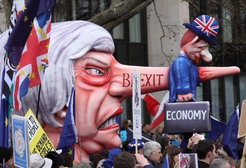 A puppet head of Britain's prime minister Theresa May spearing a representation of the British Economy is taken on the march. Photograph: Isabel Infantes/AFP/Getty Images