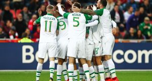 The Ireland players celebrate with Jeff Hendrick. Photo: INPHO/James Crombie