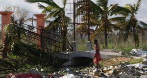 A woman searches for materials to rebuild her home after the passage of Cyclone Idai, in Beira City, central Mozambique. Photograph: Tiago Petinga/EPA