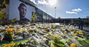 Yellow flowers are displayed in front of the portrait of Emiliano Sala at the Beaujoire stadium in Nantes. Photograph: Getty Images