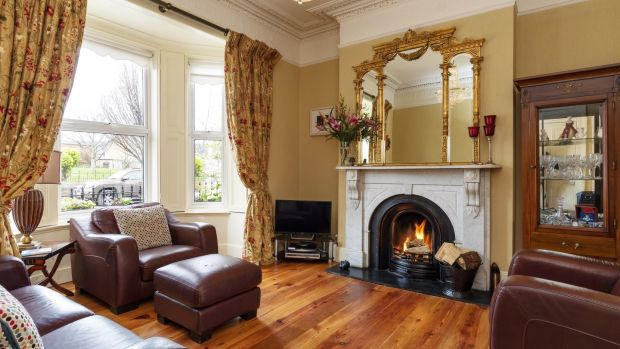 The sitting room has a white marble fireplace and restored pitch pine floor