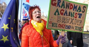 "An anti-Brexit campaigner holds  a ""Grandmas against Brexit"" placard as she protests outside parliament in London. Photograph:  Getty Images"