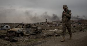 A Syrian Democratic Forces (SDF) fighter walks past destroyed vehicles in the final Islamic State encampment in Baghouz on Sunday. Photograph: Chris McGrath/Getty Images