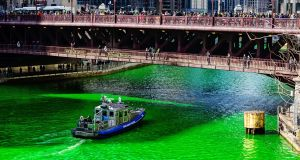 A police boat on the Chicago river dyed green for St Patrick's Day. Photograph: iStock/Steve Geer