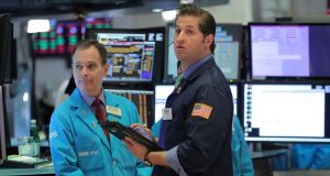 Traders work on the floor of the NYSE. Wall Street's main indexes swung between gains and losses on Thursday.