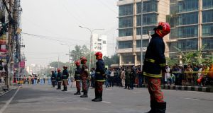 Firefighters stand guard at the high-rise block where a fire killed at least 25. Photograph: Monirul Alam/EPA