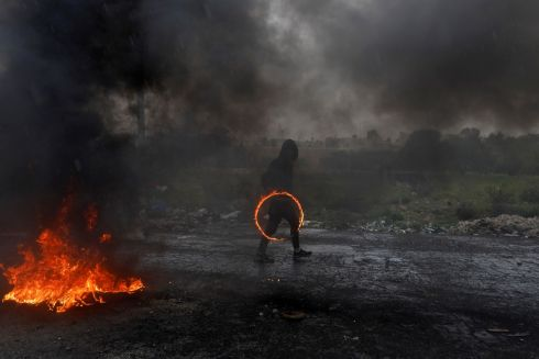 CIRCLE OF FIRE: A Palestinian demonstrator carries a burning circular object during clashes with Israeli forces at a protest marking Land Day, near the Jewish settlement of Beit El, in the Israeli-occupied West Bank. Photograph: Mohamad Torokman/Reuters