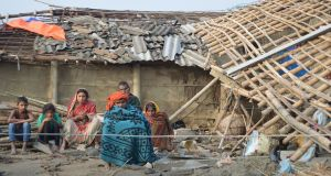 A Nepali family sits in front of their damaged home in Nepal's southern Bara district near Birgunj on April 1st, 2019, the morning after a rare spring storm. Photograph: Diwakar Bhandari/AFP/Getty