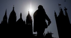 A member of the public is silhouetted against the Houses of Parliament in London, England.  Photograph:  Dan Kitwood/Getty Images