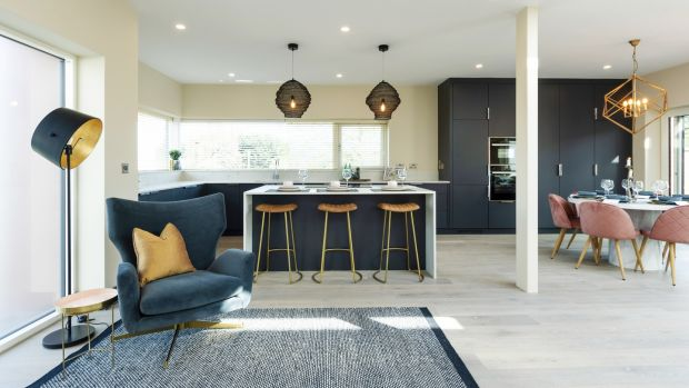 Open plan area includes dark gray Rhatigan & Hick kitchen