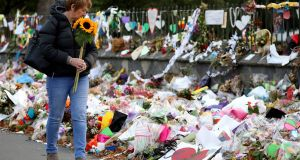 A woman walks past flowers and tributes displayed in memory of the twin mosque massacre victims at the Botanical Garden in Christchurch on March 29th. Photograph:  Sanka Vidanagama/AFP