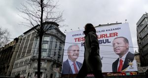 People pass in front of a banner with pictures of Turkish president Recep Tayyip Erdogan and Binali Yildirim, AKP's local candidate, in Istanbul on Tuesday. Photograph: Erdem Sahin/EPA