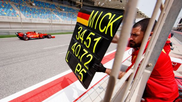 A Ferrari mechanic shows the time board to Mick Schumacher during his first testing for the Formula One team at the Bahrain International Circuit. Photograph: Valdrin Xhemaj/EPA
