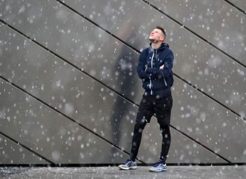 ALL HAIL: A young man assesses his chances of getting wet as commuters make their way home during a sudden shower of hail in the Grand Canal Dock area of Dublin. Photograph: Colin Keegan/Collins Dublin