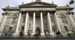 Cyclists pass the Four Courts on the Dublin quays. A route for a long-awaited Liffey cycle path has been announced by the National Transport Authority. Photograph: Nick Bradshaw/ The Irish Times