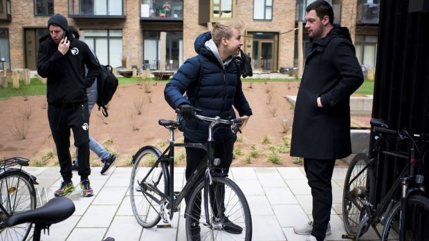 Team Origen's Jonas Andersen, centre, chats to head coach André Guilhoto as the team departs by bike for a workout. Photograph: Pete Kiehart/ The New York Times