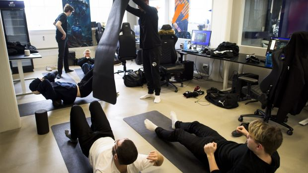 Team Origen stretches in the training room following a scrimmage against another team at Rfrsh Entertainment's offices in Copenhagen. Photograph: Pete Kiehart/ The New York Times