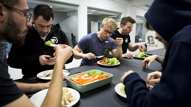 Team Origen eat a dinner of salmon and vegetables at Rfrsh Entertainment's offices in Copenhagen. Photograph: Pete Kiehart/ The New York Times