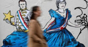 A woman walks past an art work depicting French president Emmanuel Macron and Britain's prime minister Theresa May  on a wall in Paris. Photograph: Reuters/Christian Hartmann