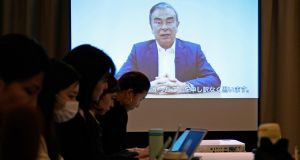 Reporters work while a screen shows a video recorded by Carlos Ghosn, during a press conference at the Foreign Correspondents' Club of Japan in Tokyo. Photograph: Franck Robichon/EPA