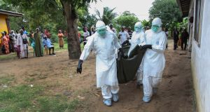 Liberian nurses carry the body of an Ebola victim in 2014. Vaccines were not available to victims of the epidemic, lobby group Access to Medicines Ireland says. Photograph: Ahmed Jallanzo/EPA