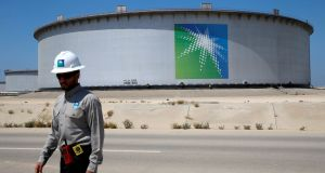 An Aramco employee walks near an oil tank at Saudi Aramco's Ras Tanura oil refinery and oil terminal in Saudi Arabia. Photograph:  Ahmed Jadallah/Reuters