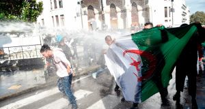 Algerian riot police use water cannon to disperse  anti-government protesters in Algiers on Tuesday. Photograph: Ryad  Kramdi/AFP/Getty Images