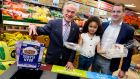 Amelia-Lily Nwanguma (5) from Rialto, Dublin gives the Minister for Climate Action and Environment, Richard Bruton and Lidl Ireland managing director JP Scally a hand to launch Lidl's new in-store recycling stations. Photograph: Maxwells