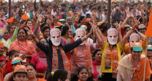 People wearing masks of Indian prime minister Narendra Modi cheer as they attend his election campaign rally at Kathua,  India on Sunday. Photograph: Jaipal Singh/EPA
