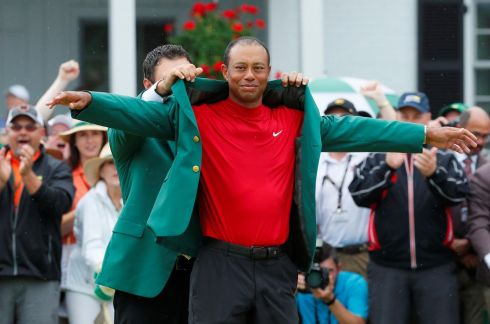 Last year's winner, Patrick Reed places the green jacket on Tiger Woods. Photograph: Reuters