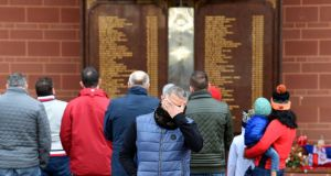 People gather in front of the Hillsborough memorial, outside of Liverpool Football Club's main stand at Anfield in Liverpool,  on Monday. Photograph: Paul Ellis/AFP/Getty