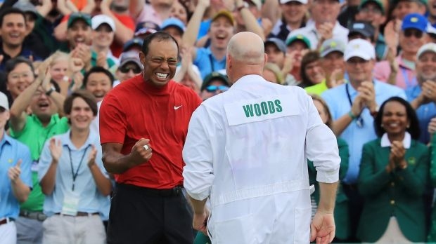 Tiger Woods celebrates with caddie Joe LaCava on the 18th green after winning during the Masters at Augusta National Golf Club. Photograph: David Cannon/Getty Images