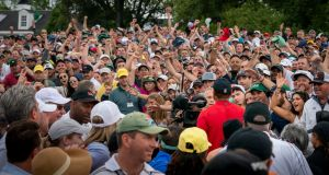 Tiger Woods walks through the crowd on the 18th hole after winning the Masters at  Augusta National Golf Club. Photograph: Doug Mills/The New York Times