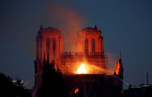 Fire fighters douse flames of the burning Notre Dame Cathedral as the two rectangular towers are illuminated. Photograph: Charles Platiau/Reuters