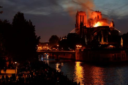 Gathered crowds line the banks of the river Seine will firefighters attept to control the blaze. Photograph: Thomas Samson/AFP/Getty