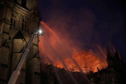 Paris Fire brigade members spray water to extinguish flames as the Notre Dame cathedral burns. Photograph: Philippe Wojazer/Reuters
