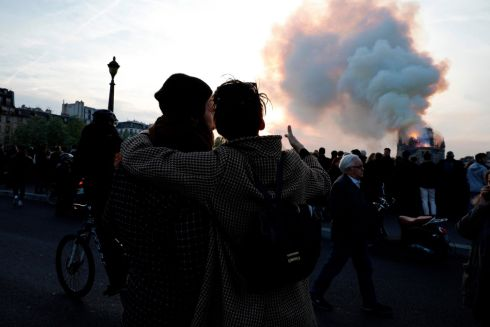 People react to the sight of fire swallowing one of the most well-known buildings in the worls. Photograph: Geoffroy Van Der Hasselt/AFP/Getty